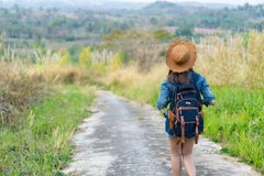 Woman with backpack walking on footpath in nature royalty free stock image