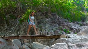 Woman with backpack walking on wooden bridge over river while hiking in mountains. Traveling woman walking on hanging. Bridge in jungle forest. Summer climbing stock video