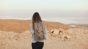 Woman with backpack walks in cloudy desert. Young thoughtful Caucasian girl wanders on dry sand, smiling. Israel 4K. Woman with backpack walks in cloudy desert stock footage