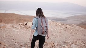 Woman with backpack walks in desert. Slow motion. Young girl wanders on dry sand and rocks. Amazing mountain scenery. Woman with backpack walks in cloudy desert stock video footage