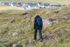 Woman with a backpack walks on the hills on the Faroe Islands royalty free stock image