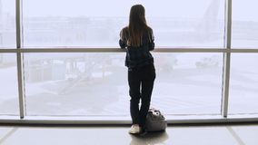 Woman with backpack walks to airport window. Happy successful European passenger girl with smartphone in terminal. 4K. Stock Image