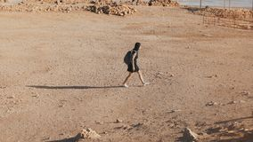 Woman with backpack walks to desert ruins. Young Caucasian female traveler on dry sand, rocks, walls. Masada Israel 4K. Woman with backpack walks to desert stock footage