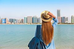 Woman with backpack weaing the hat. On the background is panorama of Abu Dhabi. The capital city of United Arab Emirates stock photography