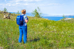 Woman backpacker came to a large lake. A middle-aged woman backpacker came to a large lake stock image
