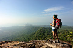 Woman backpacker climbing to mountain peak Royalty Free Stock Photo