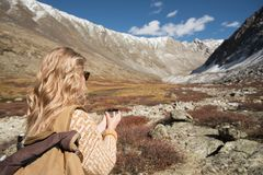 Woman backpacker in cozy clothes trekking in mountains royalty free stock images