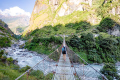 Woman backpacker crossing suspension bridge in Himalayas Nepal Stock Photo