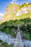 Woman backpacker crossing suspension bridge in Himalayas Nepal Royalty Free Stock Image