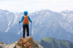 Woman backpacker enjoy the view on mountain peak cliff. Successful woman backpacker enjoy the view on mountain peak cliff stock photography