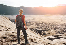 Woman with backpacker enjoying sunrise at desert canyon. Young woman backpacker traveling along mountains and desert, female walking  discovering world, summer Stock Photo
