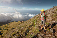 Woman with backpacker enjoying view sunset in mountains. Traveler looking at sunset in high mountains above the clouds royalty free stock photo