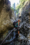 Woman backpacker going down in a gorge Stock Image