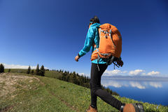 Woman backpacker hiking on beautiful mountain peak trail Stock Photography