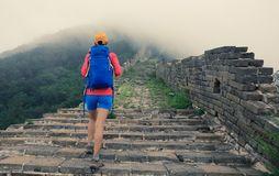 Backpacker hiking on the great wall in china. Woman backpacker hiking on the great wall in china royalty free stock images