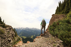 Woman backpacker hiking  on mountain peak cliff Royalty Free Stock Photos