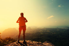 Woman backpacker hiking on mountain peak cliff Royalty Free Stock Photography