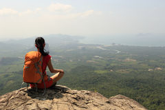 Woman backpacker hiking on mountain peak cliff Royalty Free Stock Images
