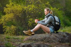 Woman backpacker hiking in summer forest and stopped to have res. T with cup of tea. Travel, hiking, backpacking, tourism and people concept royalty free stock photos