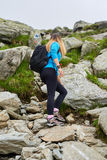 Woman backpacker hiking on a trail Stock Photos