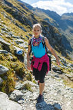 Woman backpacker hiking on a trail Stock Image