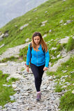 Woman backpacker hiking on a trail Royalty Free Stock Images