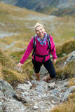 Woman backpacker hiking on a trail Stock Images