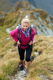 Woman backpacker hiking on a trail Royalty Free Stock Photo