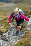 Woman backpacker hiking on a trail Royalty Free Stock Image