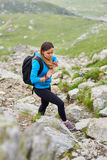 Woman backpacker hiking on a trail. Young woman hiker with backpack walking a trail in rocky mountains Stock Photos