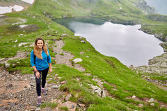 Woman backpacker hiking on a trail. Young woman hiker with backpack walking a trail in rocky mountains Stock Photo