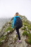 Woman backpacker hiking on a trail. Young woman hiker with backpack walking a trail in rocky mountains Royalty Free Stock Images