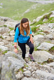 Woman backpacker hiking on a trail. Young woman hiker with backpack walking a trail in rocky mountains Royalty Free Stock Photos