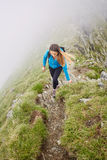 Woman backpacker hiking on a trail. Young woman hiker with backpack walking a trail in rocky mountains Royalty Free Stock Image