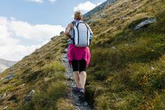 Woman backpacker hiking on a trail Royalty Free Stock Photos