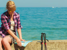 Woman backpacker with map by seaside. Adventure, summer, tourism active lifestyle. Young woman backpacker looking at map by seaside, plan her sightseeing Stock Image
