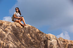 Woman backpacker and photo camera hiking in the mountain peak Royalty Free Stock Images