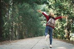 Woman backpacker in the road and forest background. Relax time on holiday concept travel ,color of vintage tone and soft focus Stock Photography