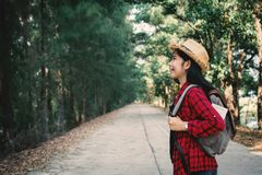 Woman backpacker in the road and forest background. Relax time on holiday concept travel ,color of vintage tone and soft focus Royalty Free Stock Images