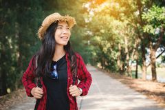 Woman backpacker in the road and forest background. Relax time on holiday concept travel ,color of vintage tone and soft focus Stock Photo