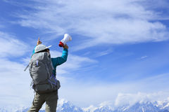 Woman backpacker shouting with loudspeaker on beautiful mountain peak. Young woman backpacker shouting with loudspeaker on beautiful mountain peak Royalty Free Stock Image