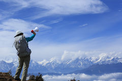 Woman backpacker shouting with loudspeaker on beautiful mountain peak. Young woman backpacker shouting with loudspeaker on beautiful mountain peak Stock Image