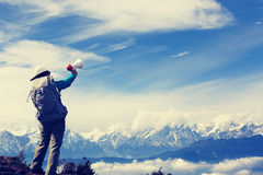Woman backpacker shouting with loudspeaker on beautiful mountain peak Stock Images
