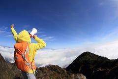 Woman backpacker shouting with loudspeaker on beautiful mountain peak Stock Image