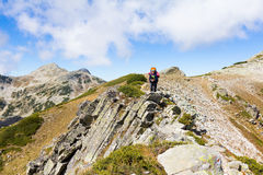 Woman backpacker standing mountain ridge. Stock Image