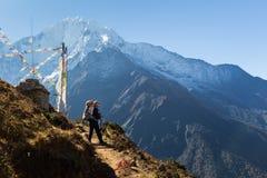 Woman backpacker standing trail, Kangtega mountain ridge snow pe Royalty Free Stock Photography