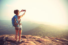 Woman backpacker taking photo with cellphone on mountain peak Royalty Free Stock Photography