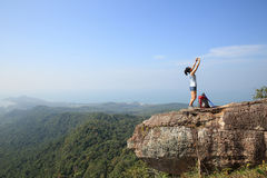 Woman backpacker taking photo with cellphone on mountain peak Royalty Free Stock Image