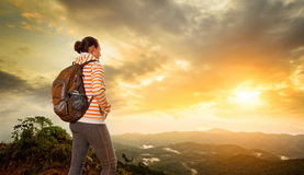 Woman backpacker traveling  with backpack standing on top of the Stock Image