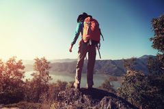 Woman backpacker trekking at mountain peak Royalty Free Stock Images